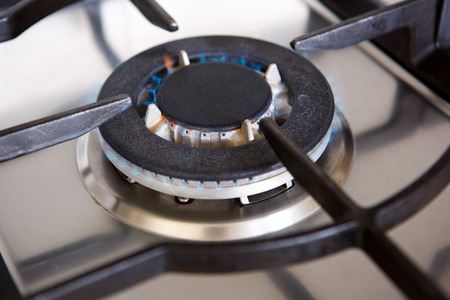 Close up portrait of gas stove top burner with flame Stock Photo