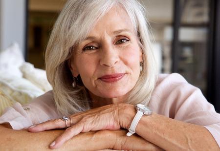 笑顔とソファの上に座ってリラックスした年上の女性の肖像画を間近します。 写真素材