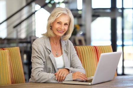 mujeres ancianas: Retrato de mujer hermosa ordenador portátil mayor trabajando en el interior