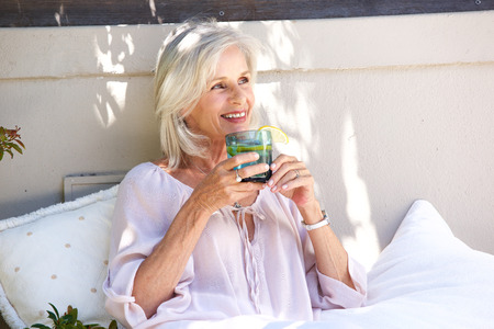Portrait of relaxed older woman outside drinking tea with lemon 스톡 콘텐츠