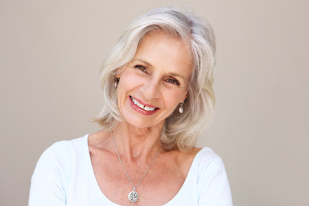 Close up portrait of beautiful older woman smiling and standing by wall Stock Photo