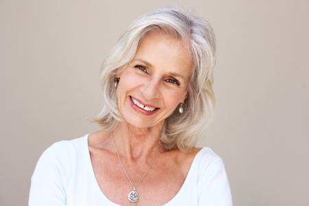 Close-up portret van mooie oudere vrouw lachend en staand tegen de muur
