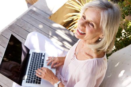 Sluit omhoog portret van gelukkige oudere vrouw met laptop computer buiten zitten