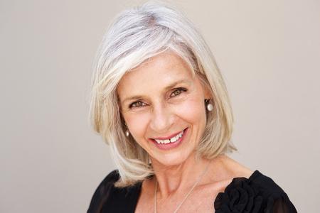Close-up portret van lachende oudere vrouw op zoek gelukkig in zwarte blouse