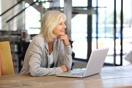 50 to 60: Portrait of smiling older woman working laptop computer indoors Stock Photo