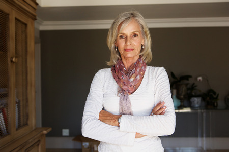 Portrait of serious older woman standing in study with arms crossed