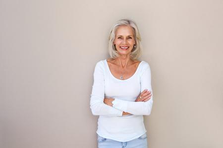 Portret van mooie oudere vrouw staande en lachend met gekruiste armen