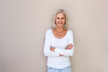 Portrait of beautiful older woman standing and smiling with arms crossed