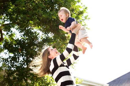 Retrato de la madre feliz que juega con el bebé afuera Foto de archivo - 75013872