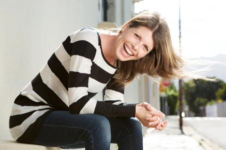 Retrato de mulher alegre sentada na rua e rindo Foto de archivo - 75013884