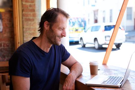 Retrato de hombre relajado sonriendo con ordenador portátil en el café