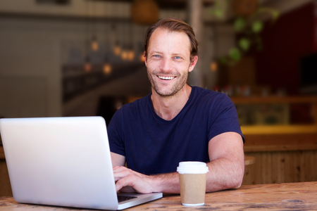 Portrait of attractive man smiling with laptop at cafe