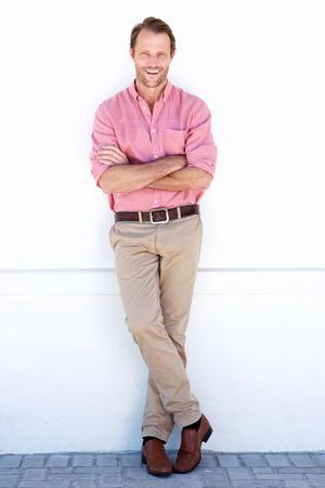 Full body portrait of handsome older man smiling against white wall