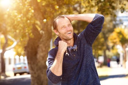 Portrait of male fashion model smiling outside in autumn