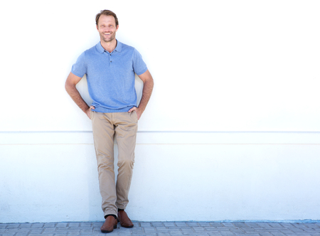 Full length portrait of handsome older man smiling against white wall