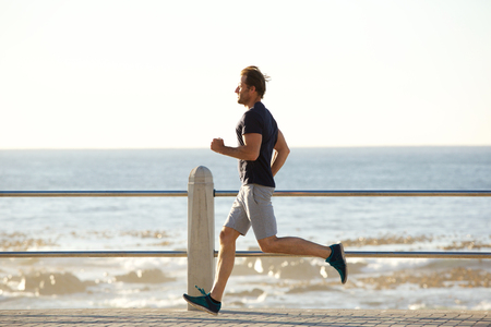 Full body side portrait of active man running by sea