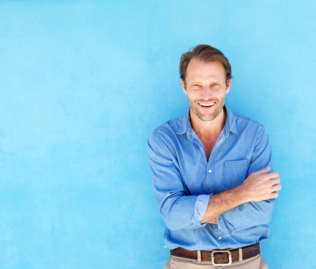 Portrait of handsome confident man smiling against blue wall