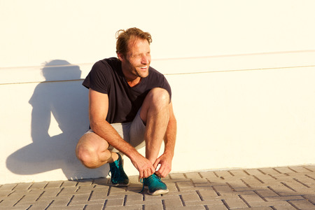 Portrait of handsome fitness man smiling and tying shoelace
