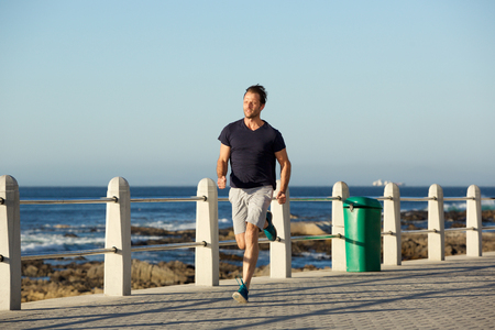 Full body portrait of middle age sports man running outside