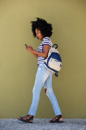 Full length side portrait of beautiful laughing woman walking with bag and smart phone