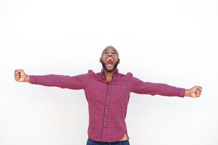 Ritratto di giovane uomo africano emozionante con le braccia tese che grida contro dalla parete bianca