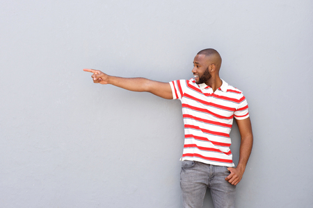 Portrait of handsome young african man pointing at copy space against gray wall