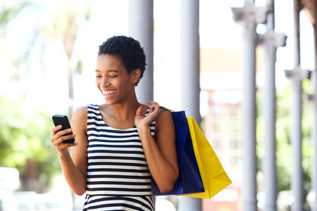 Portrait of happy young african american woman walking with cellphone and shopping bags 스톡 콘텐츠