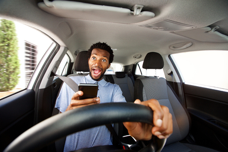 Close up portrait of distracted man driving in car holding phone