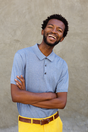 Portrait of handsome black man smiling with arms crossed