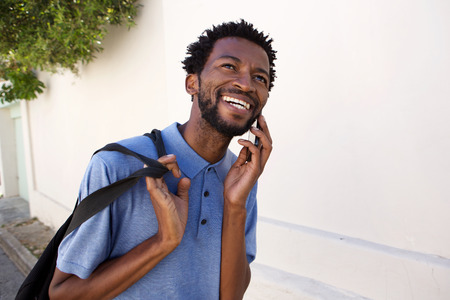 telephone call: Portrait of smiling black man walking outside on telephone call