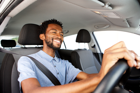 Close up side portrait of happy african american man driving car