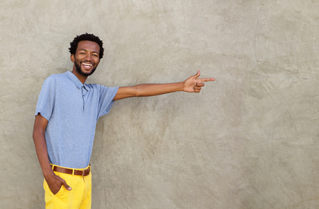 Portrait of cheerful african american man pointing to wall
