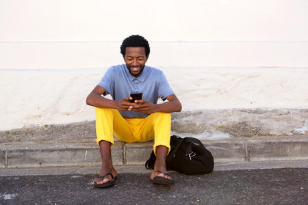 Full body portrait of happy black man sitting outside with bag and phone