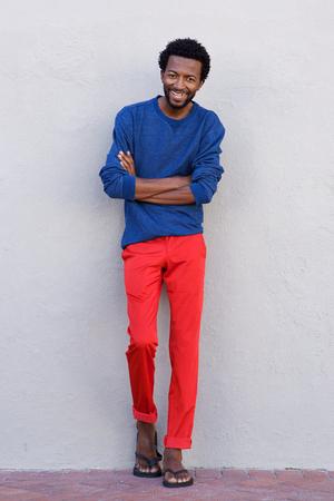 Full body portrait of handsome african american man smiling with arms crossed Stock Photo