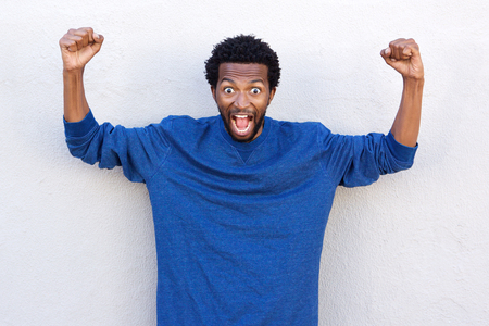 Portrait of african american man with hands raised in shock and disbelief