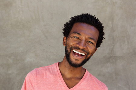 Close up portrait of attractive african man smiling by wall