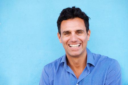 Close-up portret van zakenman lachen tegen blauwe achtergrond