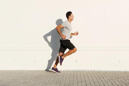 白い壁で走っている中年男の側の肖像