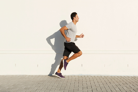 Side portrait of middle age man running by white wall