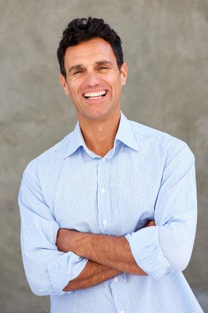 Porträt des hübschen reifen Mannes, der mit den Armen gekreuzt lächelt Standard-Bild - 77424152