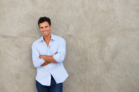 Portrait of smiling handsome middle age man standing by wall