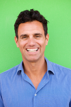 Portret van glimlachende zakenman tegen groene muur Stockfoto