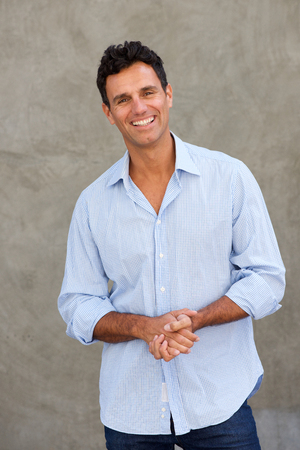 Portrait of casual businessman smiling against wall
