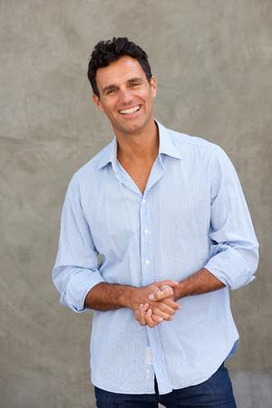 Portret van toevallige zakenman die tegen muur glimlachen Stockfoto