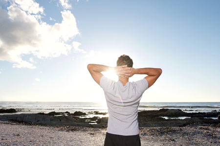 Back man looking at sea with hands behind head