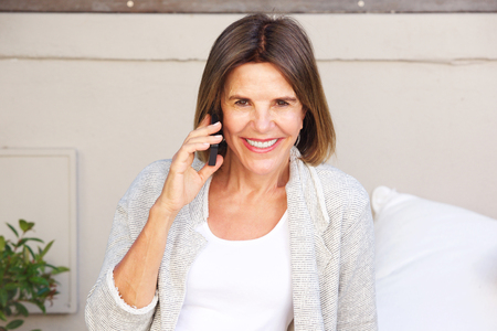 Portrait of attractive older woman smiling and talking on cell phone