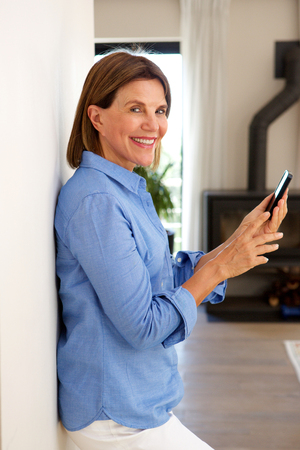 Side portrait of smiling older woman using mobile phone and home Imagens