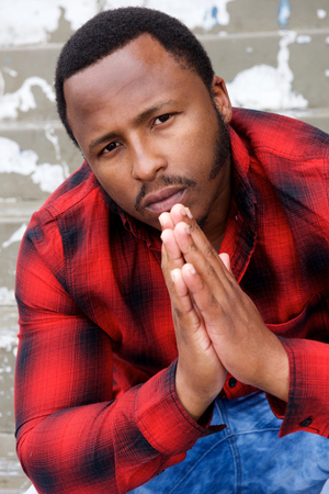 suave: Close up portrait of young black man sitting down and praying with hands clasp Stock Photo