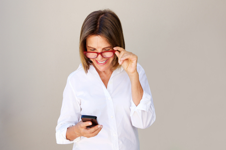 Portrait of businesswoman with glasses looking at cellphone Stock Photo