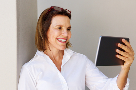 Portrait of businesswoman smiling and looking at digital tablet